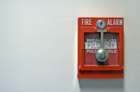 A close-up photo of a bright red fire alarm with space for text on the left