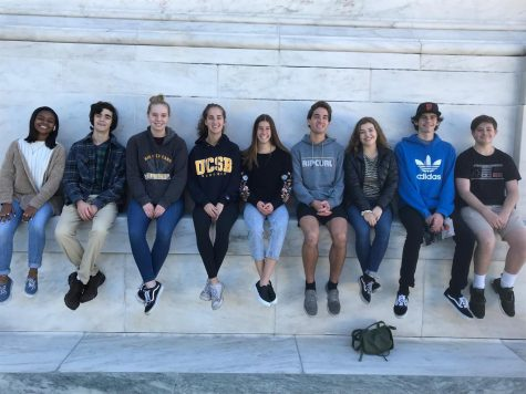 [left to right] Synia Thrower, Joseph Bender, Jessica Sheppard, Annalee Gorman, Katie Newton, Nicolas Gorman, Emma Hutchinson, Mickey Doolittle, Luke Richards sit on the outside of the United States Supreme Court.