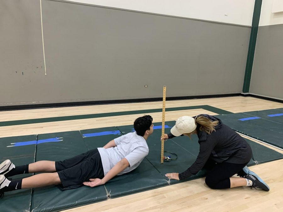 PE Teacher Shawna Virga measures a student's performance in the trunk lift for freshman fitness testing.