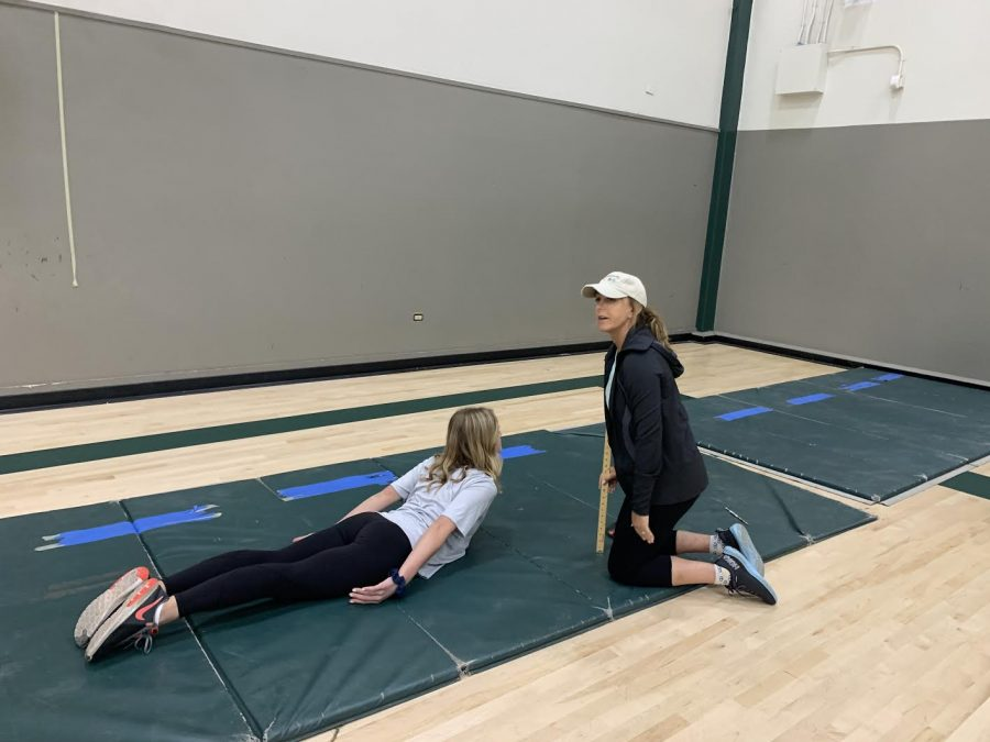 P.E. teacher Shawna Virga measures a students performance in the trunk lift exercise.
