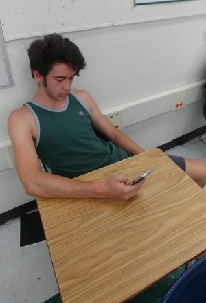 Photo illustration of student using his phone wasting valuable class time; an epidemic among classrooms.