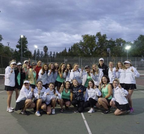 Women's varsity tennis hold up the number one as they finish first in league play Oct. 19.