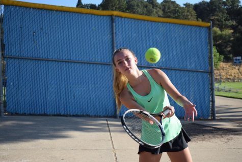 Junior Claire Chally warms up in her tennis match.