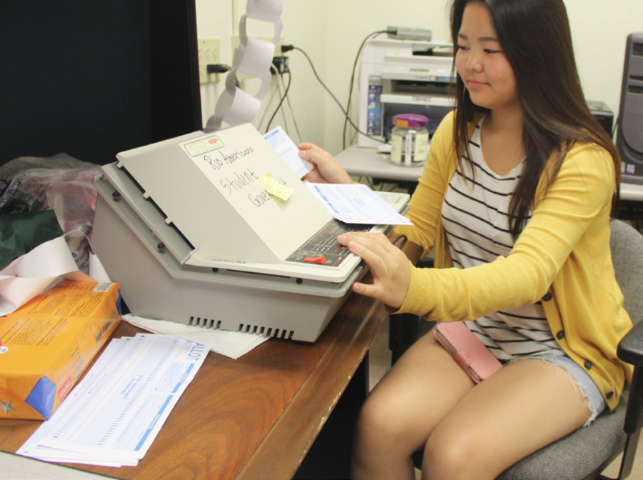 Elections Chair Yeagee Jung counts ballots with the Scantron machine before it broke.