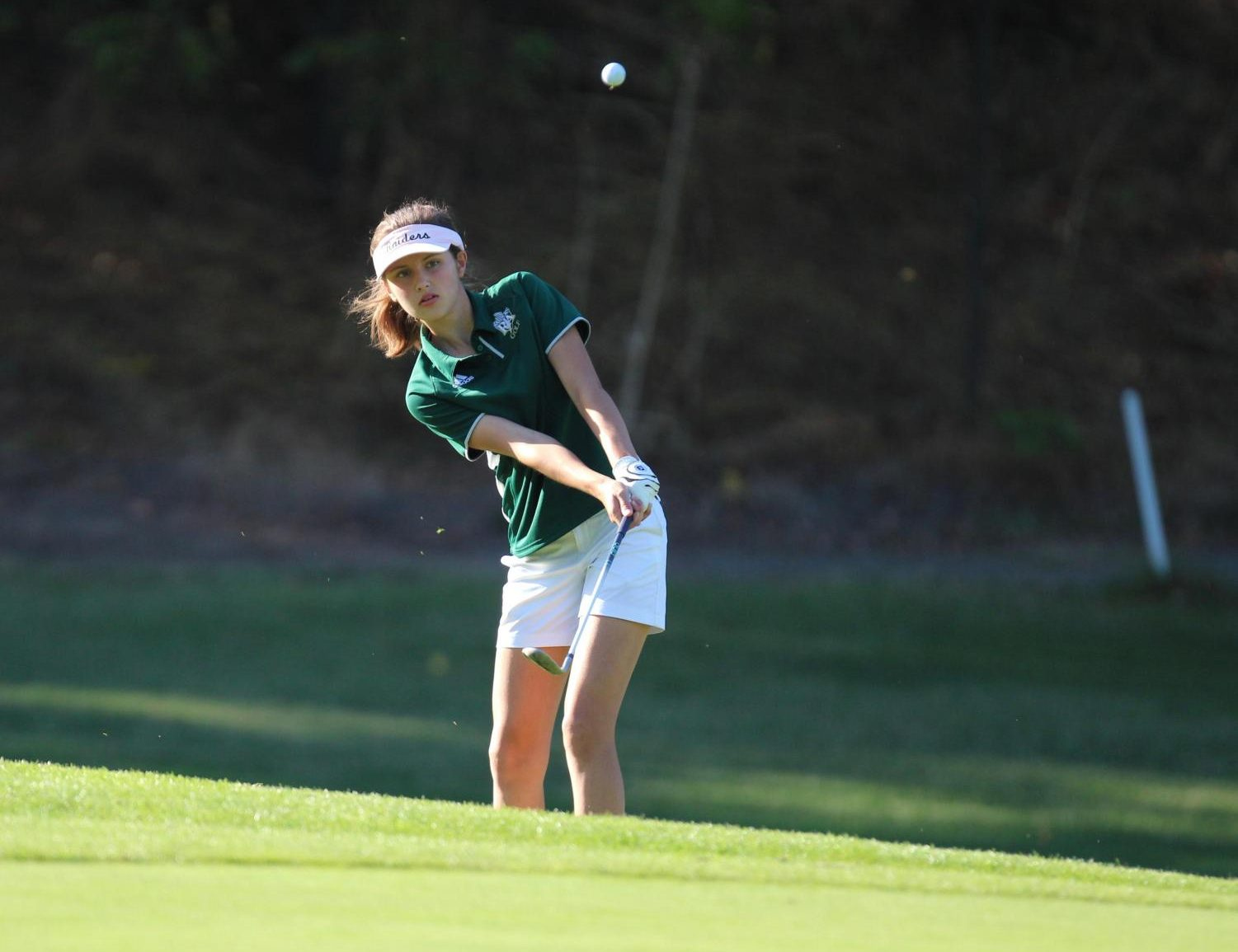 Junior Katelyn Kamilos chips the ball out of the rough. Photo by Ed Mahone.