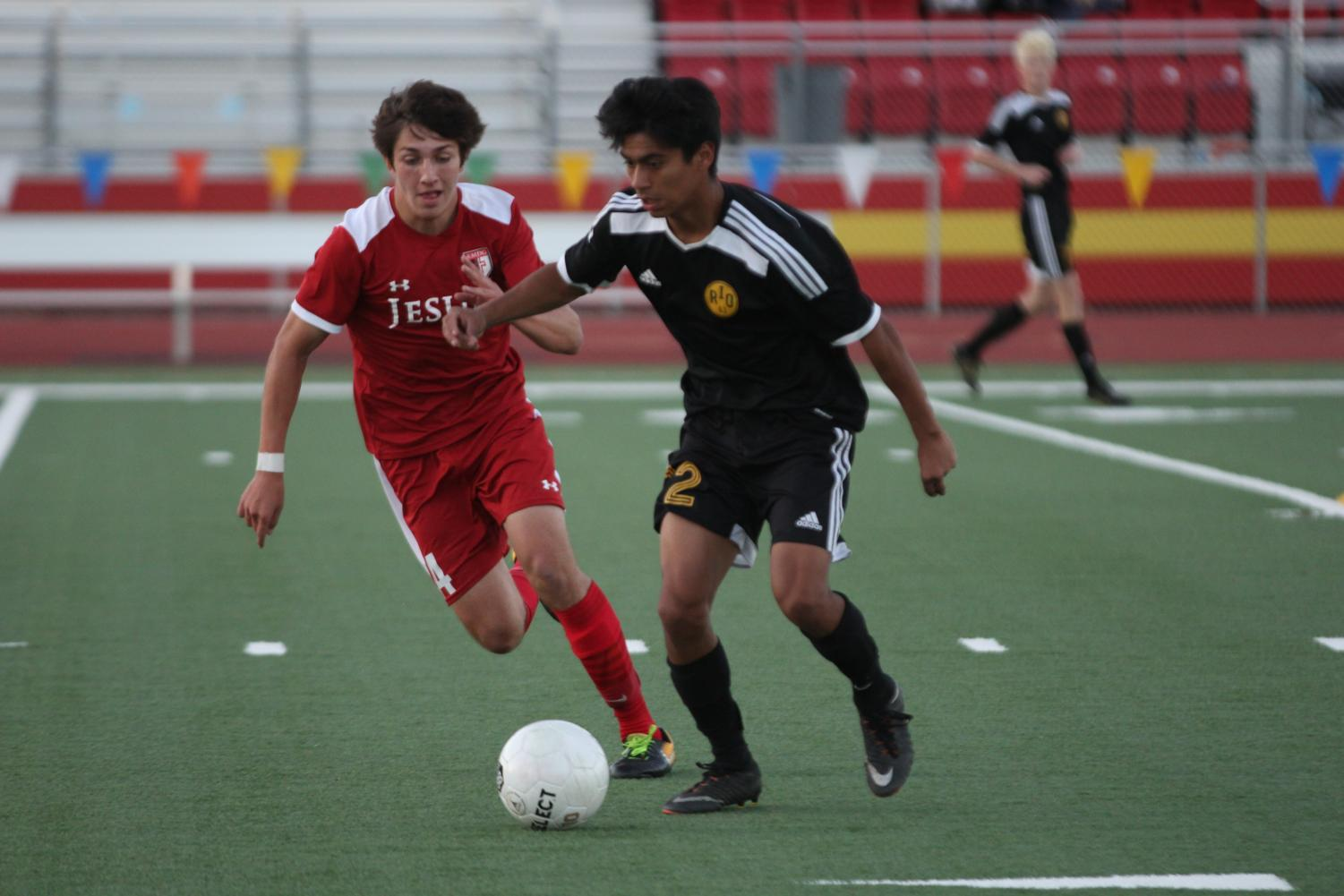Sophomore Steven Barreto holds off the defender whiling looking for an open teammate to pass the ball to against Jesuit.