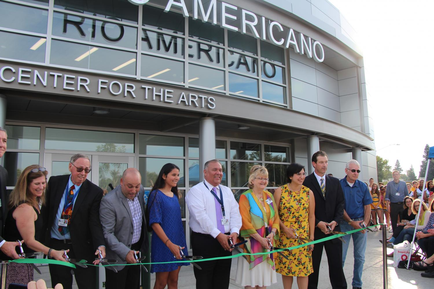 Music Director Josh Murray (third from left), Principal Brian Ginter (second from right) and district officials cut the ribbon to officially open the new theater.