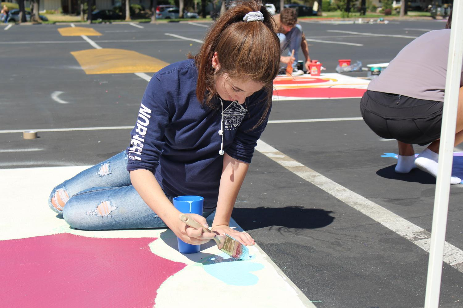 Senior Ellie Carey adds detail to her flower themed parking spot as her classmates work on theirs. Parking lot painting day was Sept. 24. In total, 86 spots were purchased.