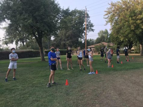 The cross country team has kept conditioning safe with small training groups, temperature checks, and mandatory masking for all runners.