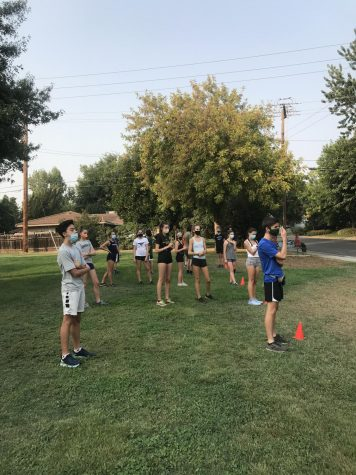The cross country team lines up in socially distant pods for conditioning.