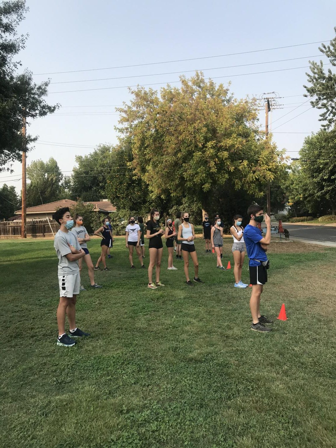 The cross country team lines up in socially distant pods for conditioning through their coach