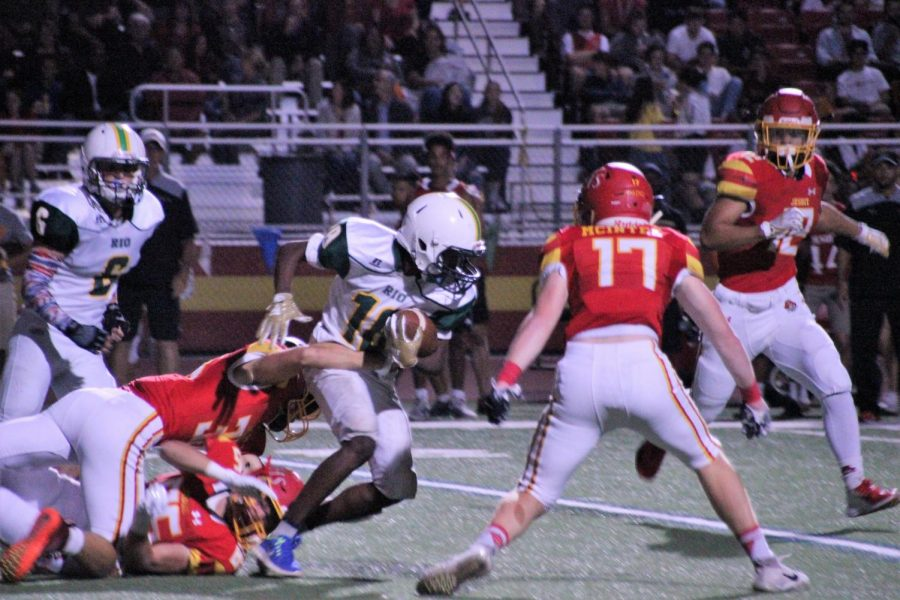 Micaiah Gautier pushes past Jesuit players while running the ball.