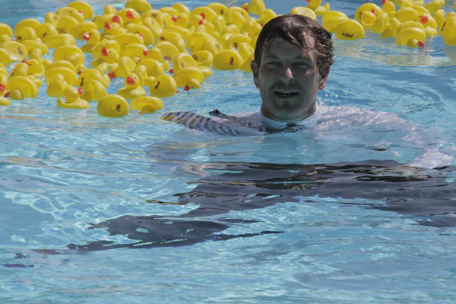 Principal Brian Ginter fishes prize-winners out of the pool on  Sept. 22 for the Duck Derby fundraiser that raised $16,008 for the school.