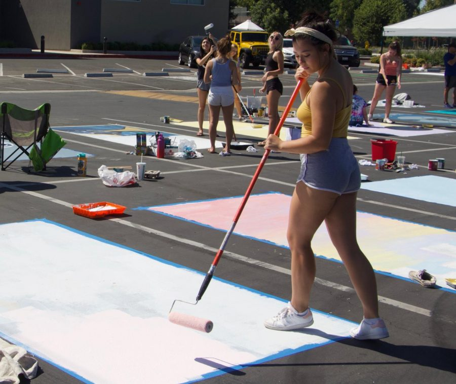 For the second year in a row, parking spots have been auctioned off to seniors as a fundraiser for Grad Night. Sat, Aug. 18 seniors and their parents spent the day in the main parking lot painting their designs onto their spot. In order to get a parking spot, the seniors paid for either the raffle style spot for $150 or the Premium Spot for $310. The seniors that paid for Premium Parking were the first group to pick their spot, and the order was based on the order that they paid. The students that bought raffle style spots had their names drawn and were divided into eight groups. At senior schedule pick up, the groups were called and picked their spots in the order listed. Students were required to buy their own supplies, including paint and rollers. At 8:30 a.m., students and their helpers arrived to beat the heat, brushes in hand. The job was long and many stayed for over 8 hours to complete their artwork. In the middle of the day the high was 100 degrees and there are estimates that the asphalt reached up to 145 degrees causing many seniors to suffer from sunburns and heat exhaustion. The artwork both beautifies the school and allows students to express their individuality: it's the biggest fundraiser for the senior class.