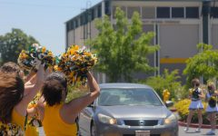 The cheer team waves their pom-poms at passing seniors.