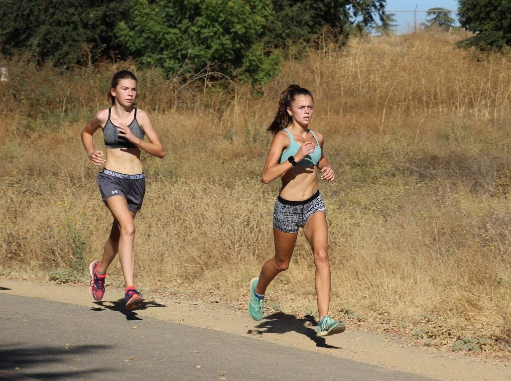 Sophomore Lucy Prieto and Freshman Josie Perez run on the levee at practice. Photo by Jane Snider